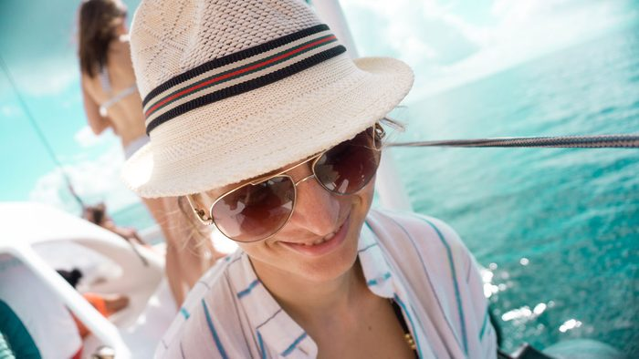 woman wearing a sun hat to protect her shiny hair