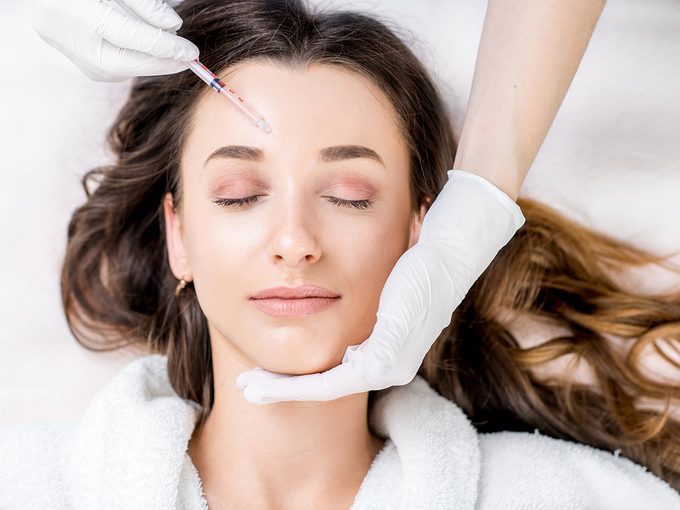 Botox before and after, Woman lies in bathroom and has Botox injected into her forehead