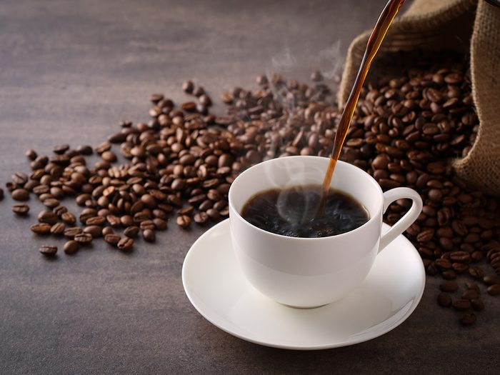 Caffeine, cup of coffee surrounded by coffee beans
