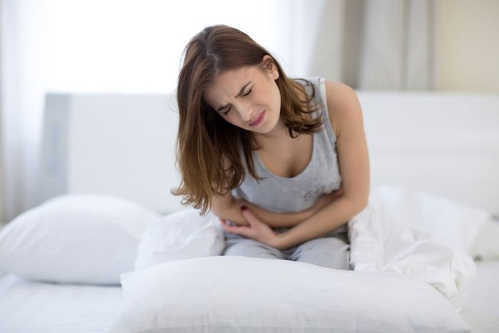 Lactose intolerant woman sits doubled over on her bed