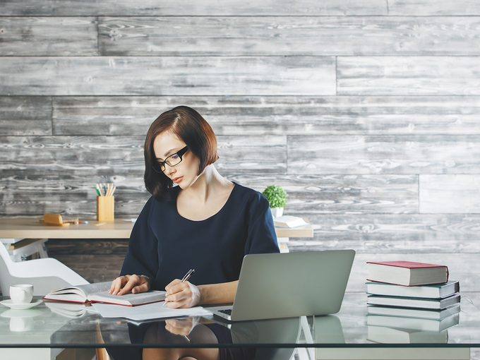 Sitting disease, Woman ssitting in her office working on a laptop at her desk