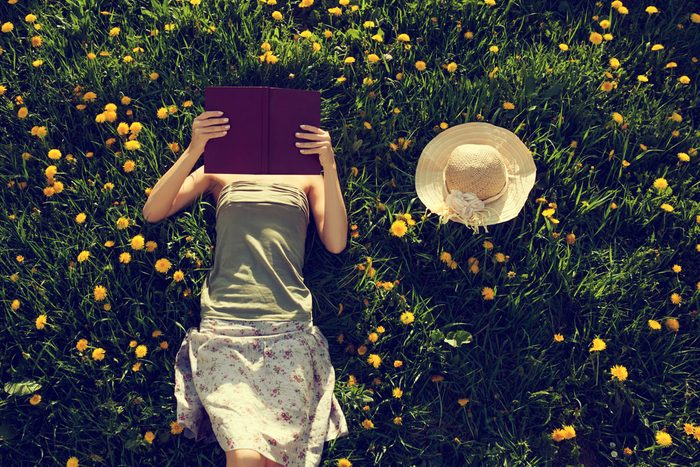 girl lying on grass and reading