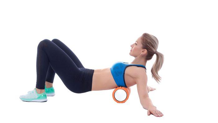 woman using foam roller on her upper back