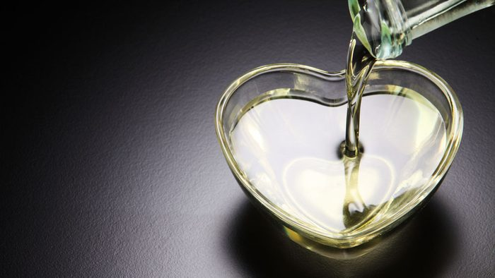 oil is being poured into a pretty heart-shaped bowl
