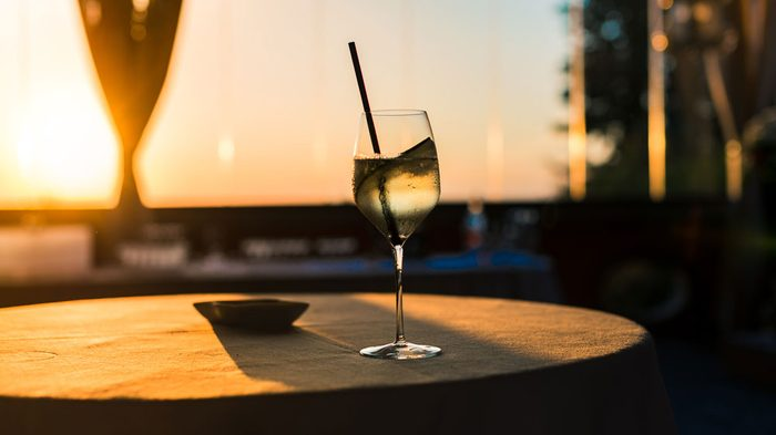 A glass of wine on a restaurant patio table at sunset