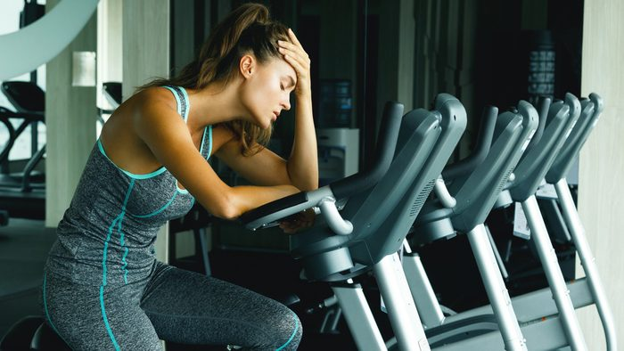 Spinning mistakes too hard: an exhausted woman its on her spin bike