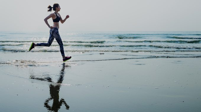 What do those blood pressure numbers mean, woman running on the beach for her cardio exercise