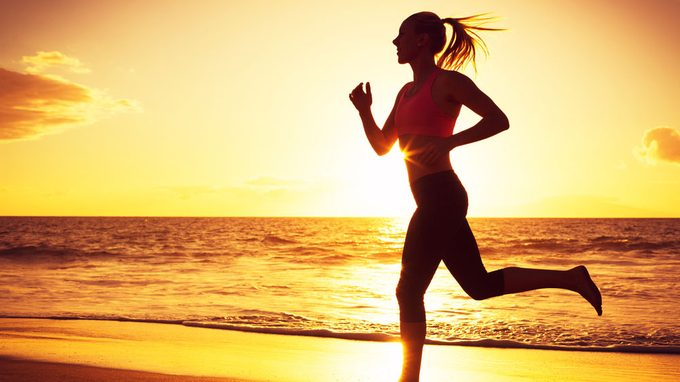 autoimmune diseases and women, a woman is running into the sun set on a beach