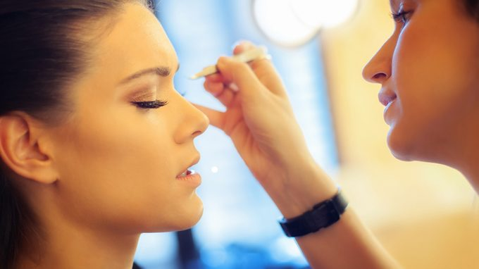 woman getting bombshell lashes put on by a makeup artist