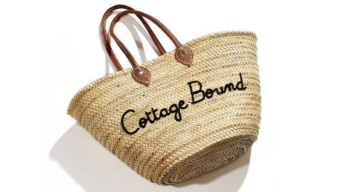 """summer layering tote, a straw bag with """"cottage bound"""" written on the front"""