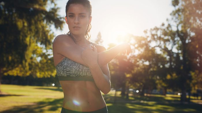 staying motivated in summer temperature, a woman outside doing stretches