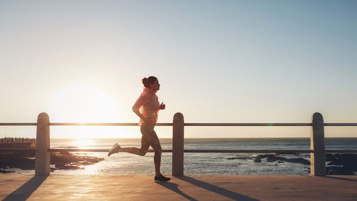 staying motivated in summer, a woman runs along a boardwalk