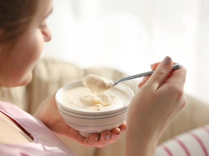 yogurt remedy for UTIs, woman eating yogurt