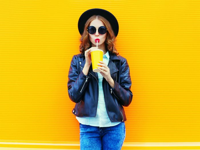 foods that fight colds, woman drinking a orange drink