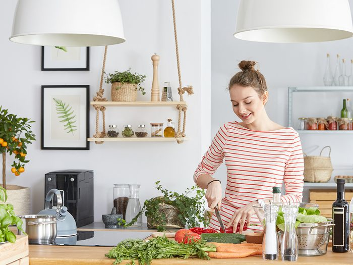 slow cooker recipes, young woman in a kitchen prepping vegetables