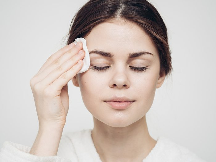 Blackheads, woman cleansing her face with a treatment pad