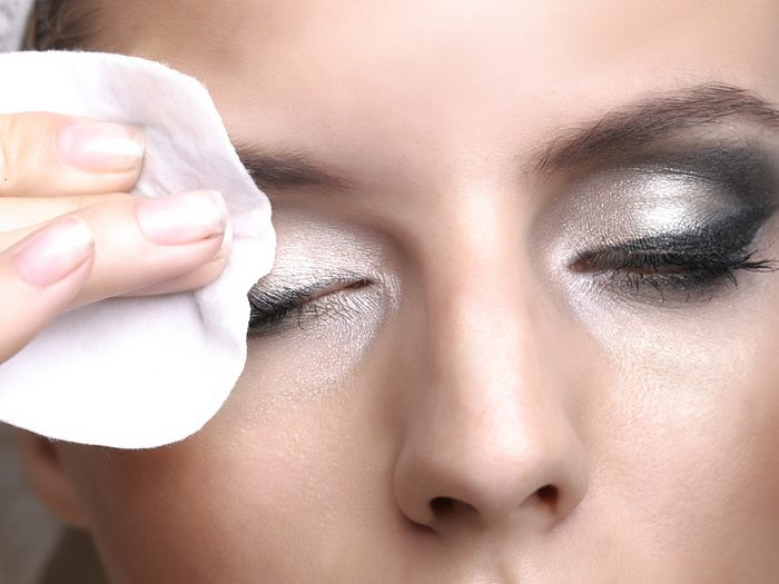 Blackheads, woman removing her eye makeup with a cotton pad