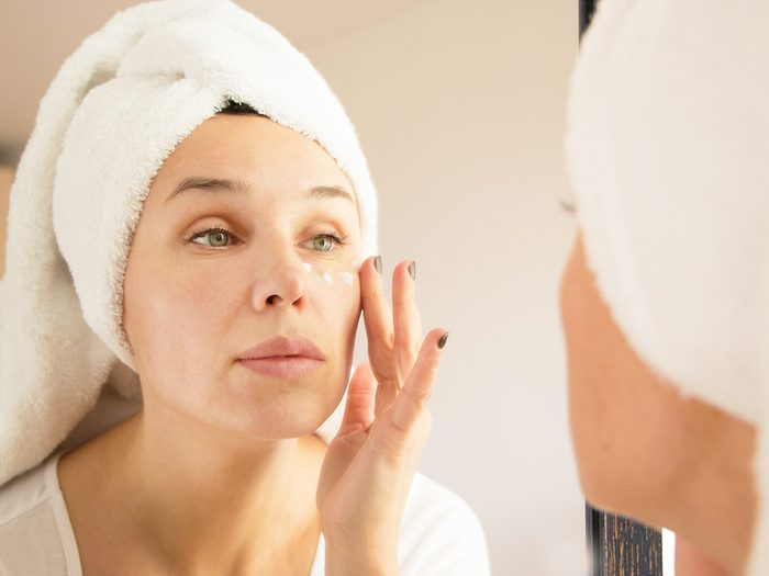 Green tea, woman with hair wrapped in towel applies eye cream