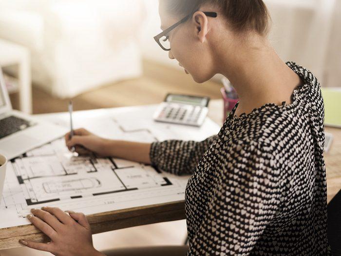 Green tea, woman works hard on floor plan at desk.