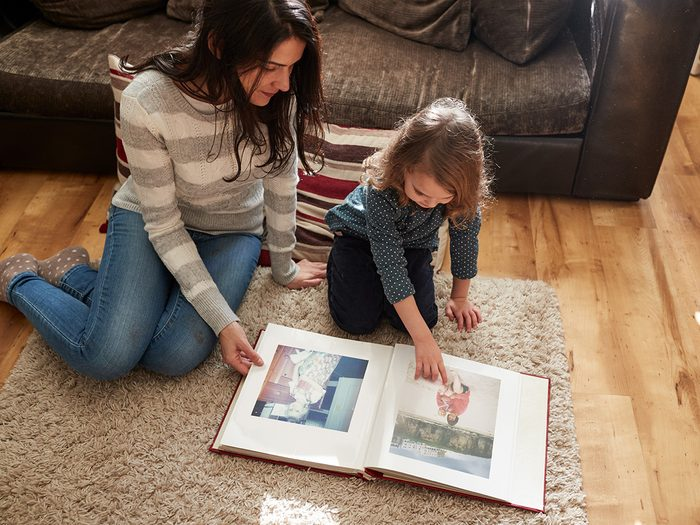 Happiness, mother and daughter sitting on the floor and looking at photo album