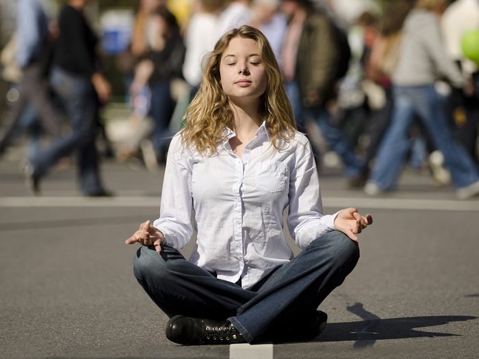 Meditation, woman meditating in the middle of a busy street