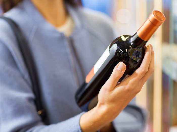 Woman checking natural wine label at store