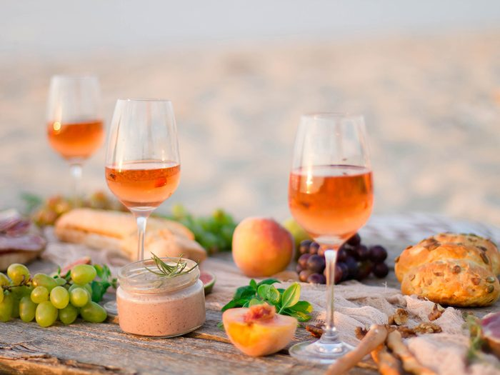 Orange natural wine on outdoor table filled with food