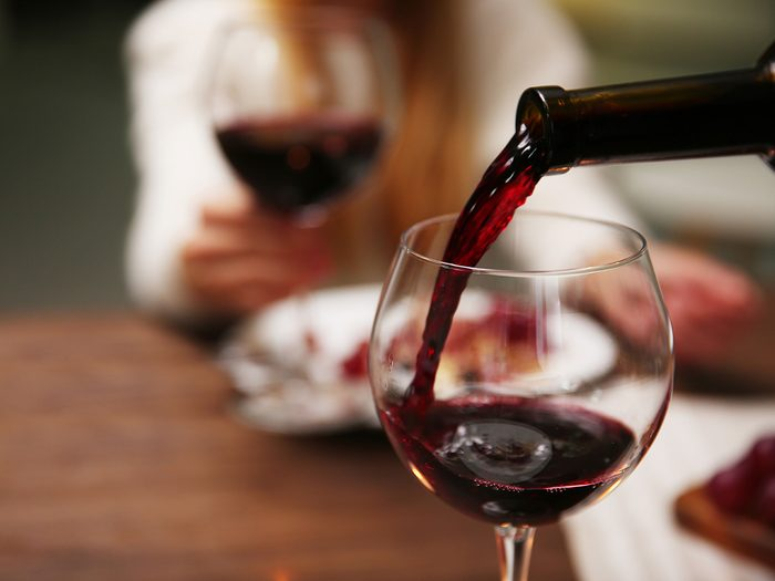 Pouring glass of red natural wine