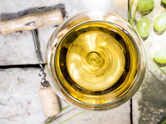 Glass of white natural wine with cork screw
