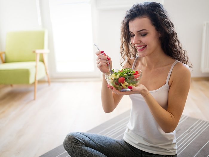 Weight loss myths, woman on yoga mat eating salad