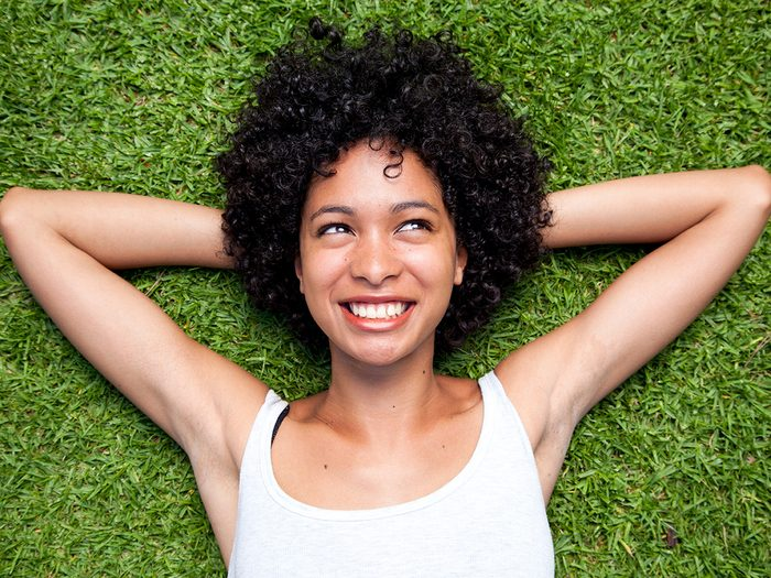 Happiness, woman smiling lying in the grass with her hands behind her head