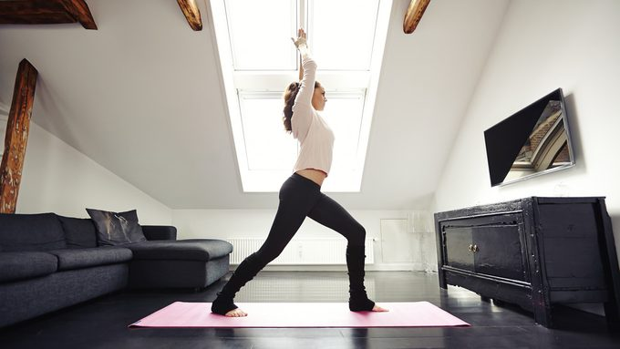motivation for yoga at home, woman practicing yoga in front of her TV
