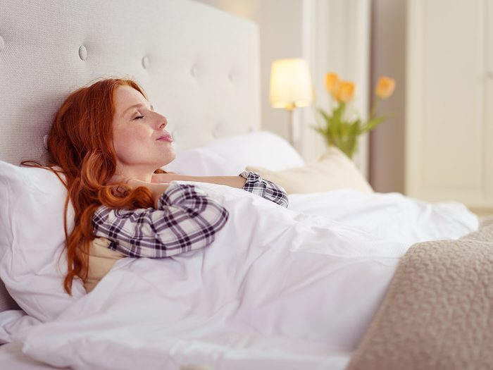 Woman with head propped up in bed to prevent heartburn