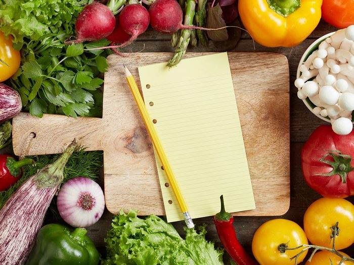 How to eat healthy, blank grocery list and pencil surrounded by vegetables