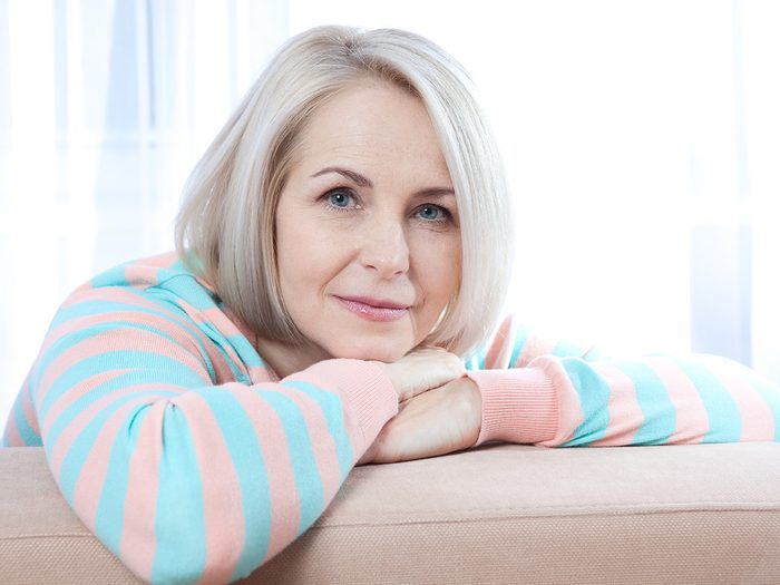 Menopause symptoms, middle-aged woman rests on couch