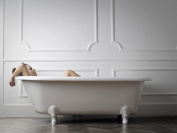 Menopause symptoms, woman takes a bath in a calm white room