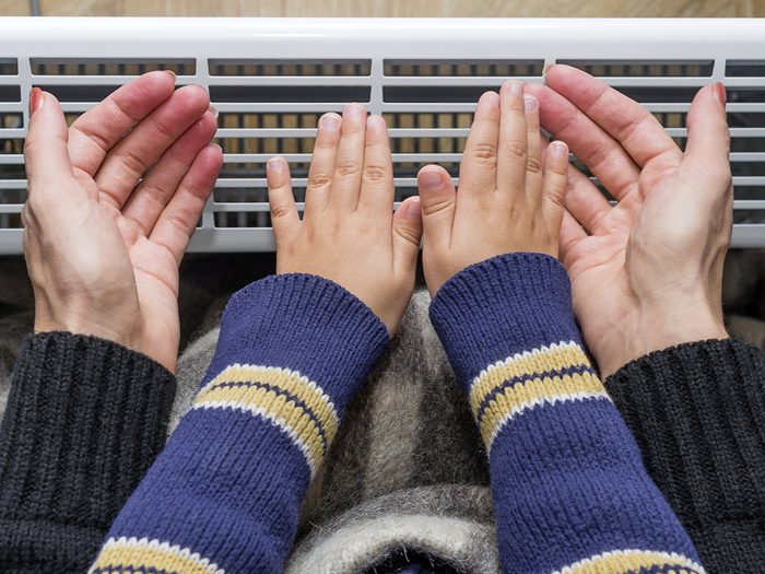 Eczema, mother and son holding their hands in front of a heater