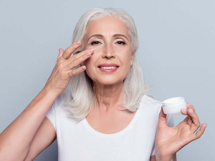 Mature woman applies cream to her face