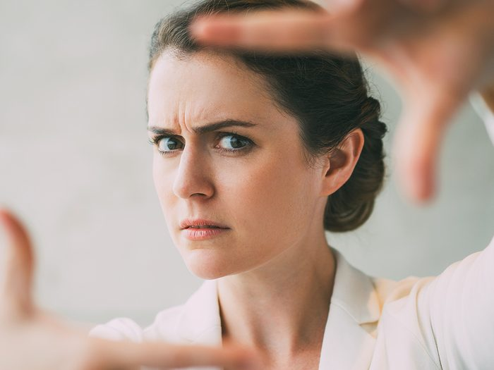 skincare, woman frowning framing her face with her hands