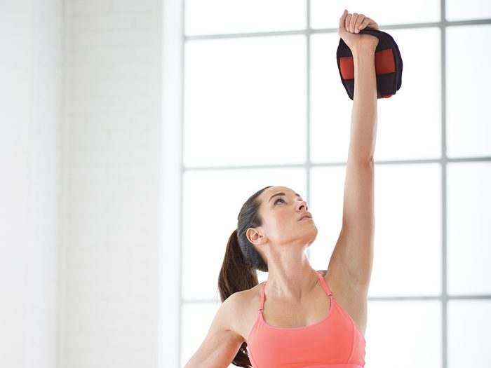 Workout gear, woman lifting a Merrithew soft kettlebell into the air