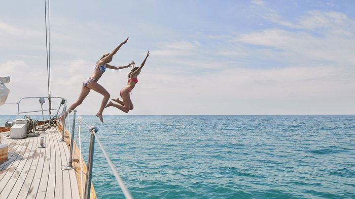 Happy People, two people jumping off of a boat