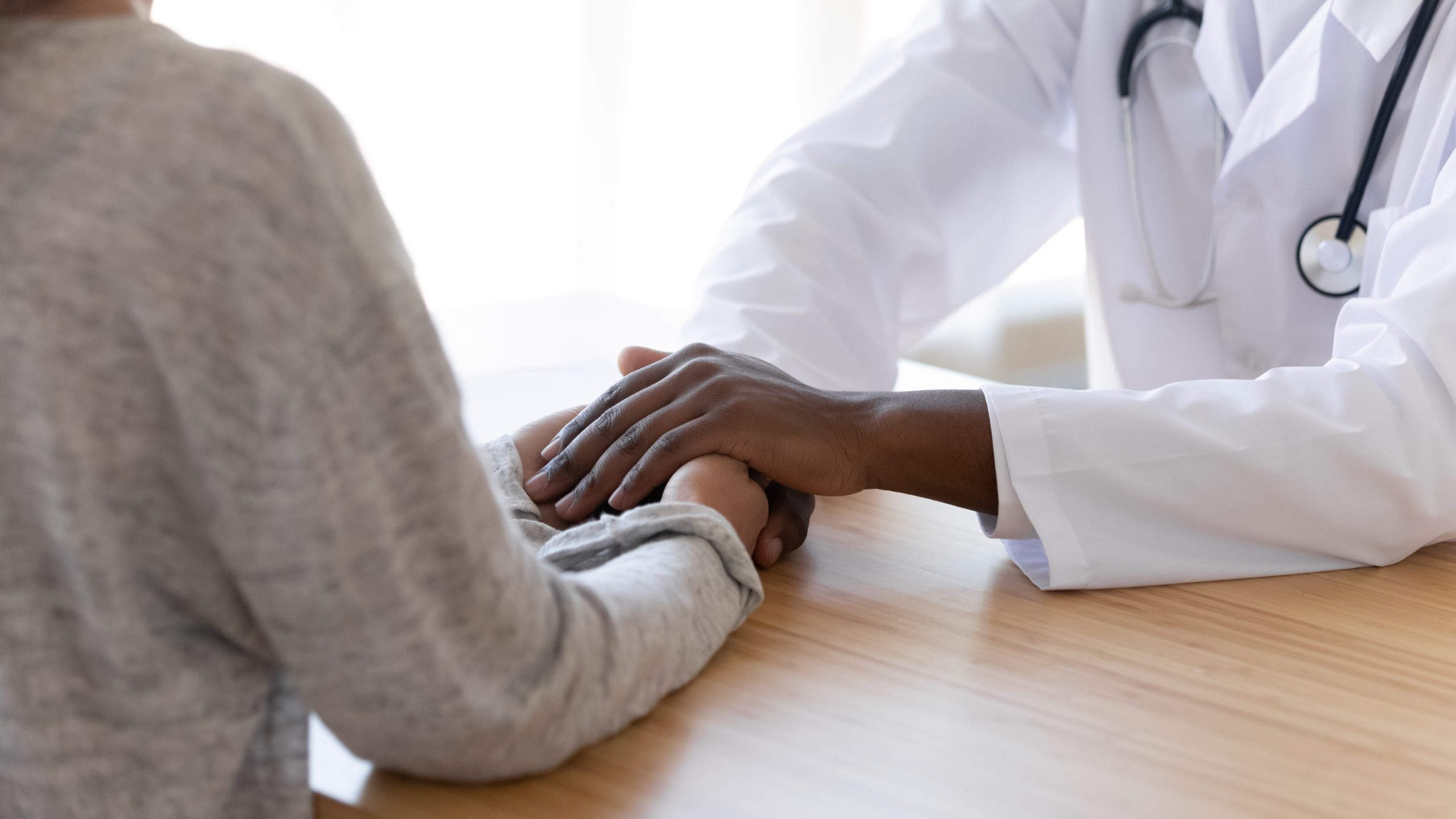 Black,male,doctor,holding,hands,of,female,patient,at,meeting