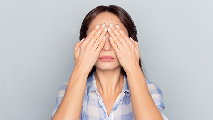 woman covering her face with hands eyes