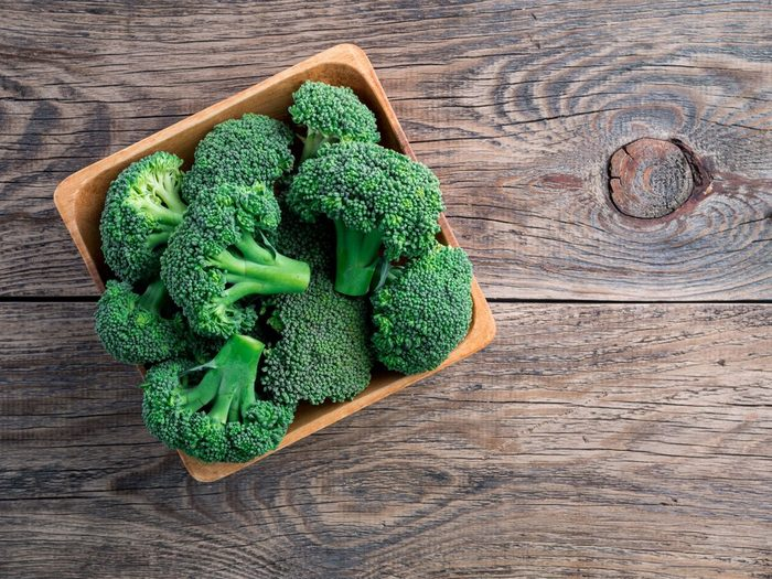 fresh raw green broccoli in wooden bowl on wooden background, top view