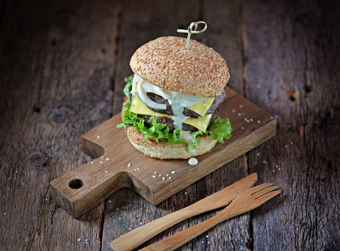 Homemade double cheeseburger with marinated onion and white sauce on a serving board on an old wooden background.