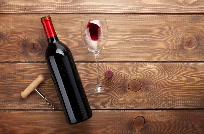 Red wine bottle, glass of wine and corkscrew. View from above over rustic wooden table background with copy space