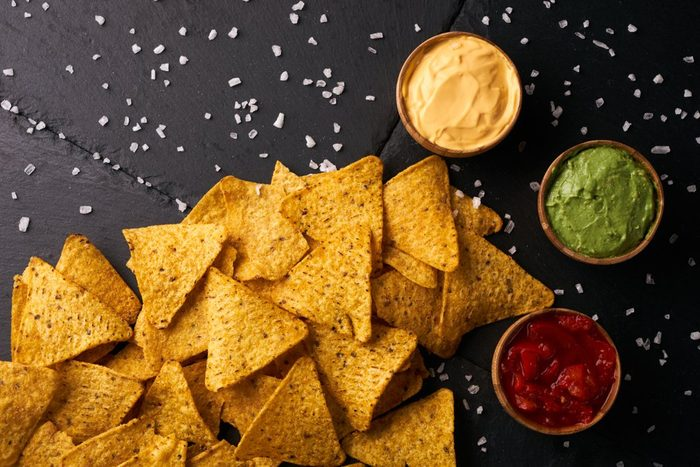 Mexican nachos with sauces tomato ketchup, cheese and guacamole in wooden bowl on dark background, top view, copy space. Delicious salty corn chips triangular nachos snack for party