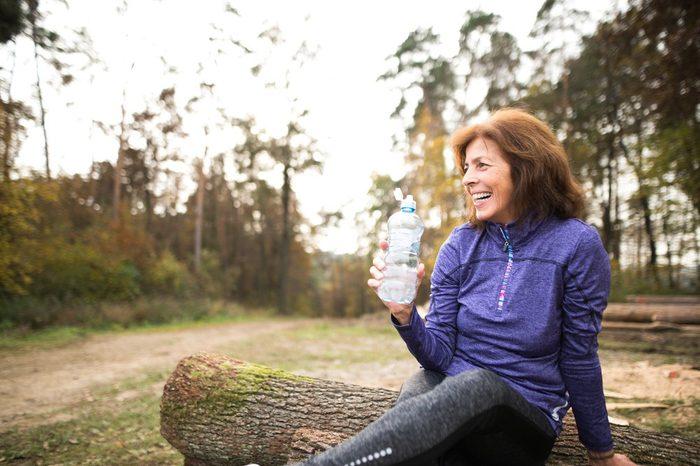 Senior runner sitting on wooden logs, resting, drinking water.