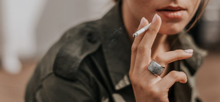 A woman's hand holds a cigarette. Smoking cigarettes. Nicotine. Smoking is bad for your health. Woman's face, lips. Smoking kills