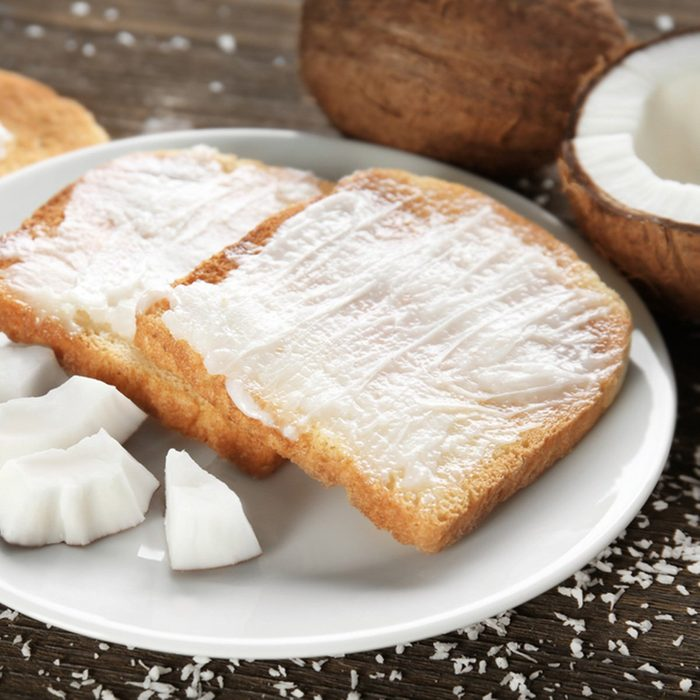 Delicious toasts with coconut oil in plate on table